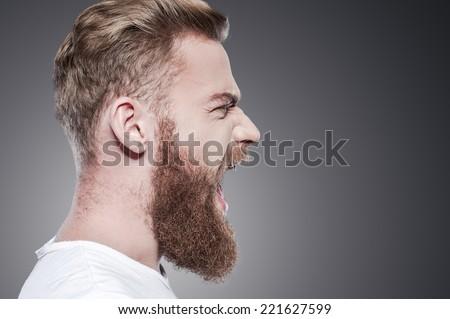Unleashing his emotions. Side view of furious young bearded man shouting while standing against grey background - stock photo