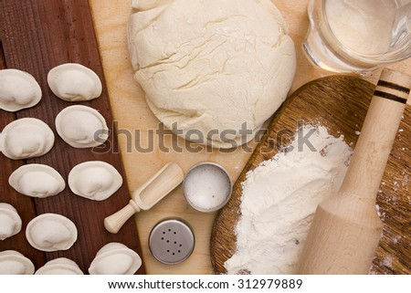 Unleavened dough with ingredients for making dumplings. - stock photo