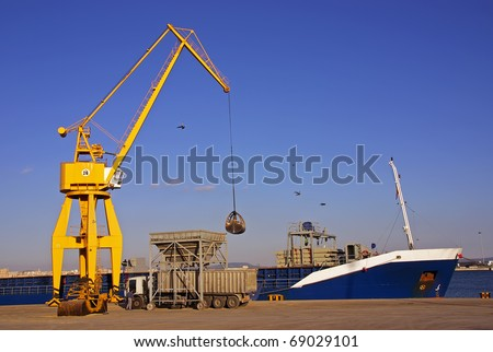 Unloading a cargo ship in the dock with a crane - stock photo