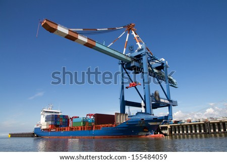 Unloading a container ship - stock photo