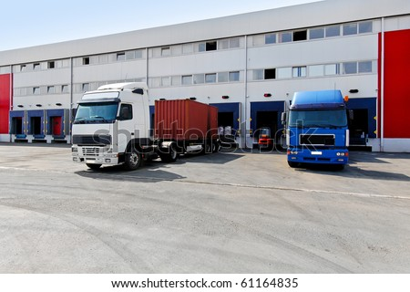 Unloading big container trucks at warehouse building - stock photo