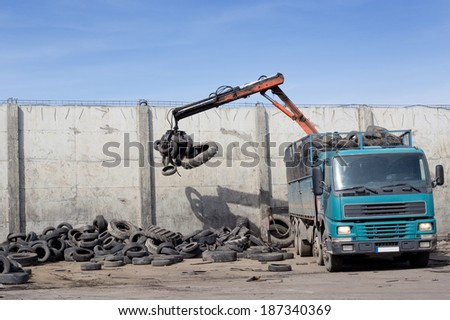 Unloading old used tires from truck for recycling - stock photo