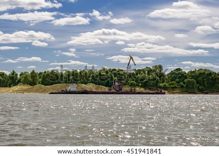 Unloading river sand barge - stock photo
