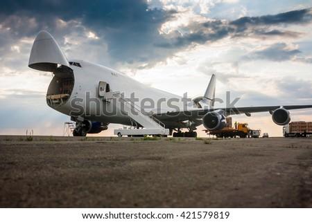 Unloading wide body cargo airplane - stock photo
