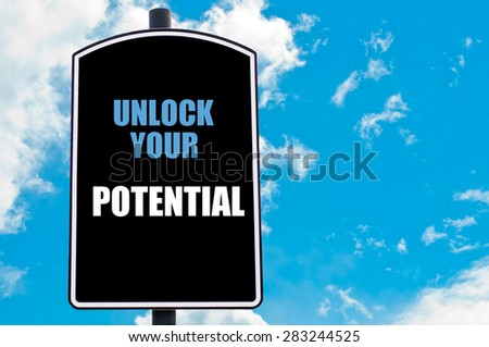 UNLOCK YOUR POTENTIAL motivational quote written on road sign isolated over clear blue sky background with available copy space. Concept  image