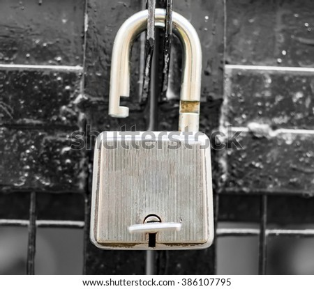 Unlocked lock on the gate with key in the hole. - stock photo
