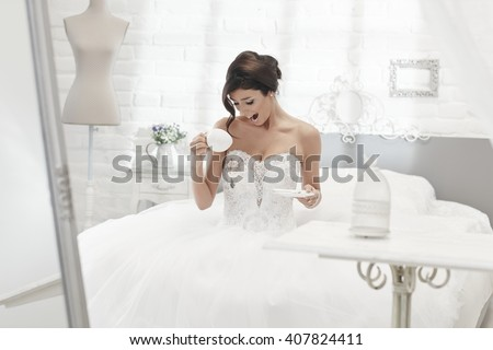 Unlucky bride spilling coffee on wedding dress, looking shocked.