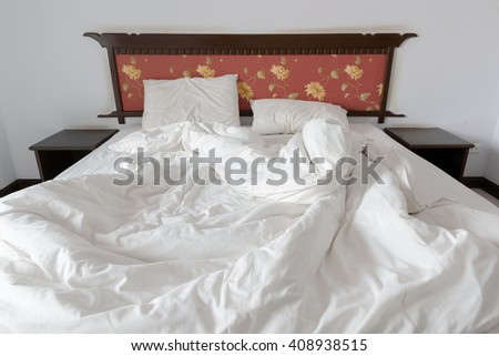 Unmade bed with a white blanket and two pillows and a teak wood headboard. Bedclothes are not neatly arranged for new customer to check in and sleep in. - stock photo