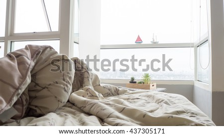 Unmade bed with crumpled bed sheet, a blanket and pillows after waking up in the morning. - stock photo
