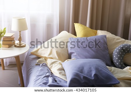 Unmade bed with crumpled blue bed linens and side table