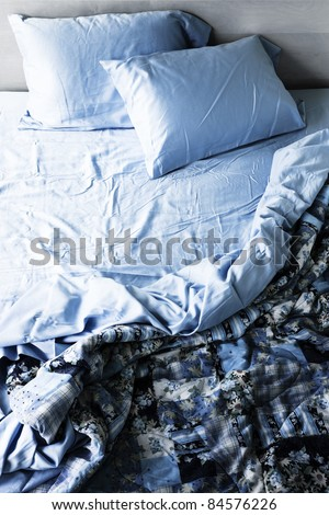 Unmade messy bed with wrinkled sheets from above - stock photo