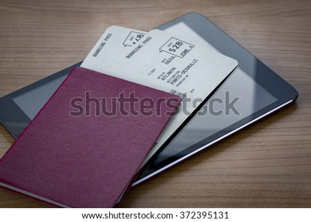 Unmarked red passport with two flight tickets on a tablet pc