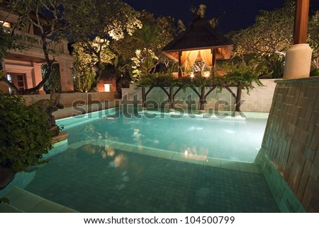 Unoccupied and lit swimming pool in Bali in dusk - stock photo