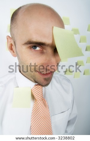 Unorganized businessman desperately uses post-it notes to somehow remember important details and schedules. - stock photo