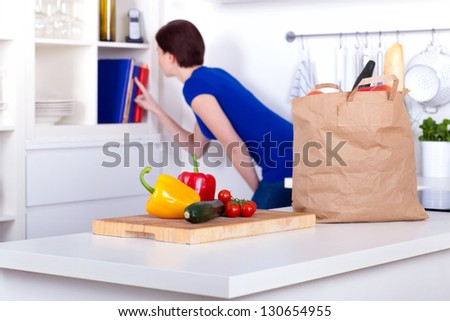 unpacked groceries in the kitchen and a woman at the cookbooks - stock photo