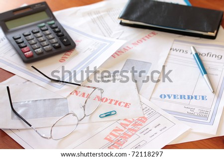 Unpaid Bills on Table with Calculator - stock photo