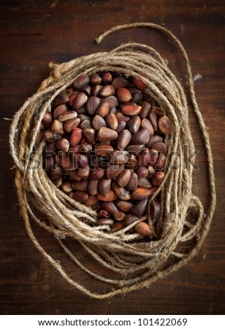 Unpeeled pine nuts on the wooden board,casual style - stock photo