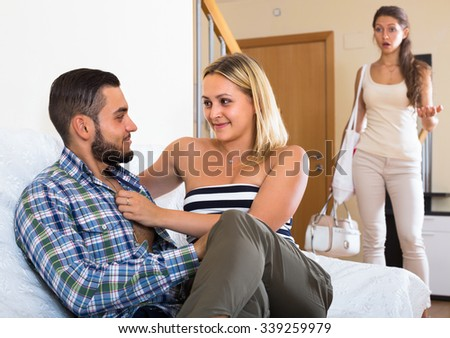 Unpleasantly surprised girl discovering her husband with another woman at home - stock photo