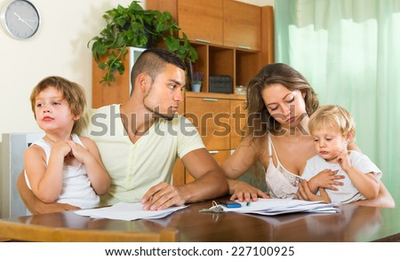 Unpleasantness about documents in young family with two kids at the table - stock photo