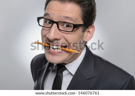 Unpleased businessman. Portrait of businessman holding a pencil in his mouth and looking at camera - stock photo