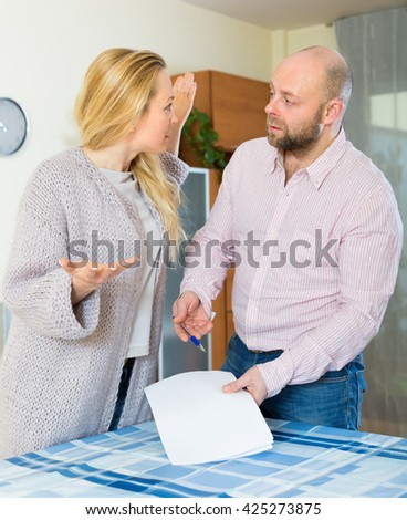 Unpleased couple having conflict over financial documents at home. Focus on woman