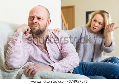 Unpleased man and woman during quarrel in living room at home  - stock photo