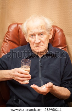 unpleased old man with a questioning look holding a glass of water and a mix of pills - stock photo