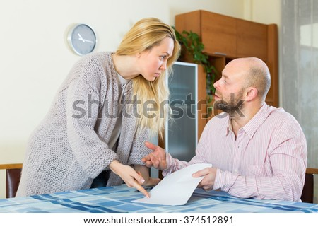 Unpleased young couple having conflict over financial documents at home - stock photo