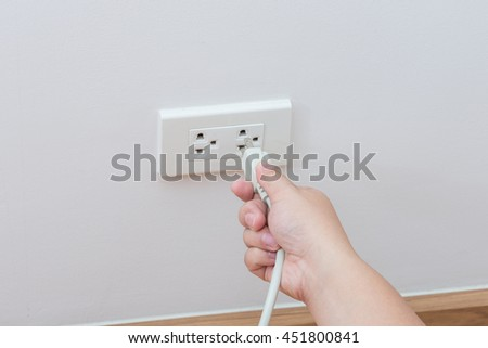 Unplug or plugged in concept,hand holding and pull electric plug