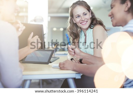 Unposed group of creative business people in an open concept office brainstorming their next project. - stock photo