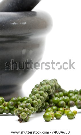 Unprocessed green peppercorns with mortar over white background - stock photo