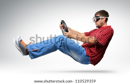 Unreal bearded funny man car driver in goggles with a wheel, auto concept - stock photo