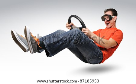 Unreal funny man car driver in goggles with a wheel, auto concept - stock photo