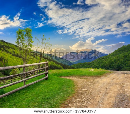 unreal summer landscape. fence near the meadow crossroad path on the hillside composite with forest on the mountain - stock photo
