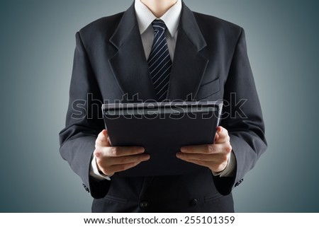 Unrecognisable businessman holding documents on blue background. Photo with place for your text. - stock photo