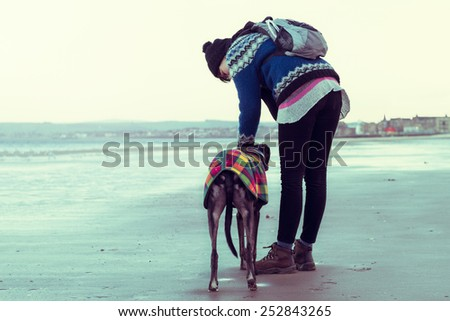 Unrecognisable hipster girl walking her dog, Greyhound, on the beach. Colorised filter effect image. - stock photo