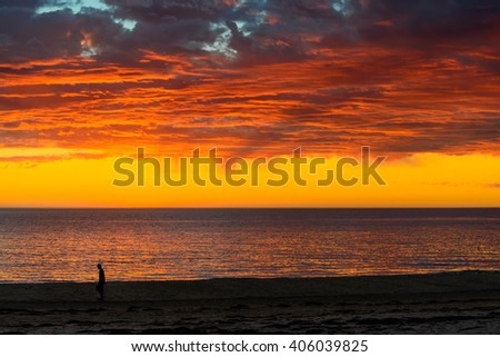 Unrecognisable man walking along the beach during dramatic sunset and storm clouds - stock photo