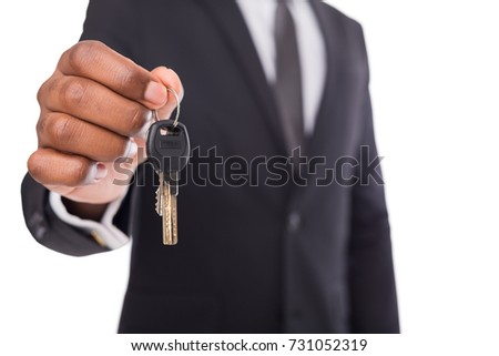 Unrecognizable african american businessman offering key of house, car or business, motivation poster, copy space