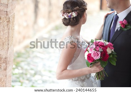 Unrecognizable bride and groom standing together on the garden - stock photo