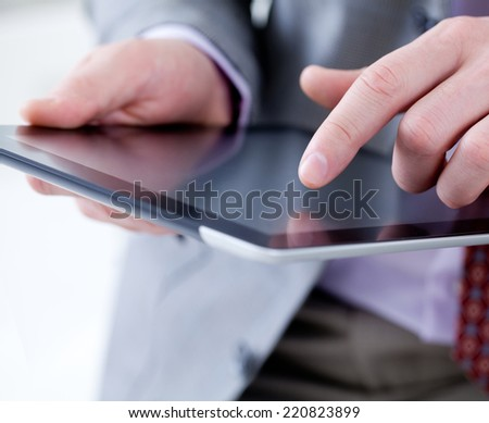 Unrecognizable business man holding a digital tablet