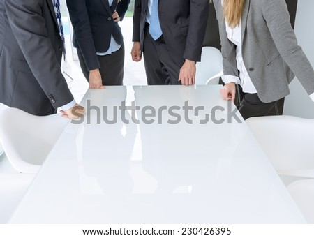 Unrecognizable business people standing around meeting table with lots of copy space - stock photo