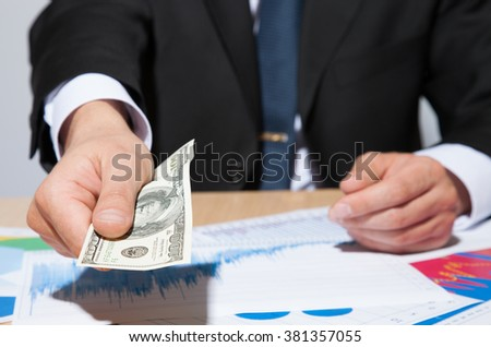 Unrecognizable businessman giving a hundred dollars, closeup shot - stock photo