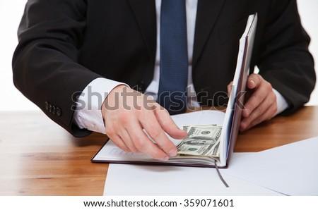Unrecognizable businessman hiding money in the book - stock photo