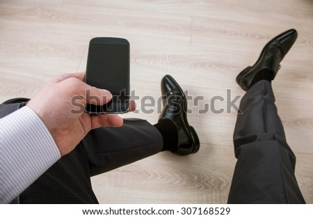 Unrecognizable businessman holding a cellphone and sitting at room - stock photo