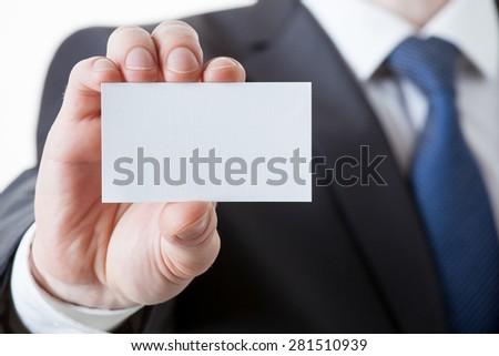Unrecognizable businessman holding a visiting card, closeup shot - stock photo