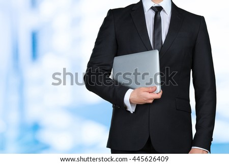 Unrecognizable businessman holding and showing laptop