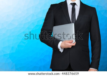 Unrecognizable businessman holding and showing laptop - stock photo