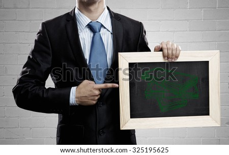 Unrecognizable businessman holding blackboard with drawn money concept
