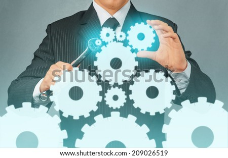 Unrecognizable businessman holds metal wrench with cogwheels, concept of business creation - stock photo