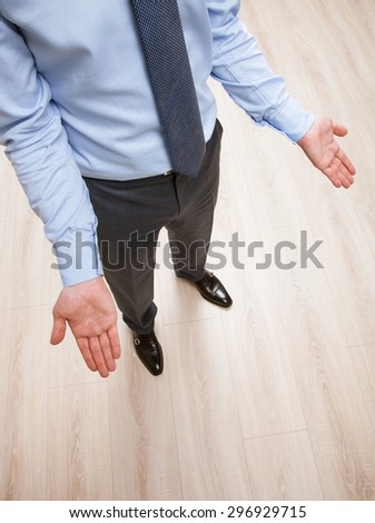 Unrecognizable businessman showing a gesture of a confusion, wooden background